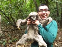 young man holding a sloth in the forest